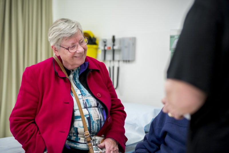 Elderly female sitting on hospital bed
